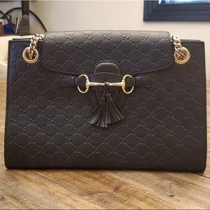 Gucci handbag with golden chain details.